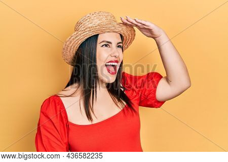 Young hispanic woman wearing summer hat very happy and smiling looking far away with hand over head. searching concept.