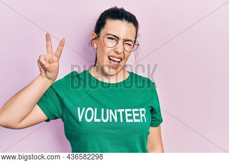 Young hispanic woman wearing volunteer t shirt smiling with happy face winking at the camera doing victory sign with fingers. number two.