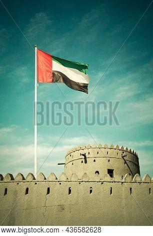 A flag of United Arab Emirates  hoisted on an ancient burj or fort. UAE National Day celebration photo.