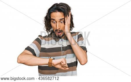 Young hispanic man wearing casual clothes looking at the watch time worried, afraid of getting late