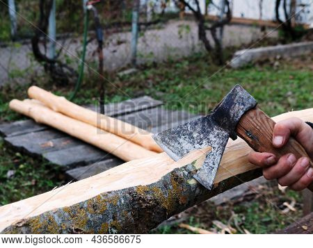 Grinding Off The Bark Of An Ash Log By A Carpenter Using A Sharp Ax, Peeling Off A Layer Of Bark Fro