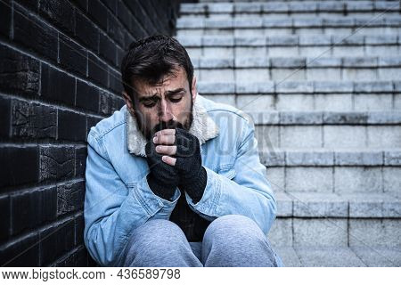 Young Sick Depressed Homeless Hobo Man With Mental Issues Sitting On The Staircase On The Urban Stre