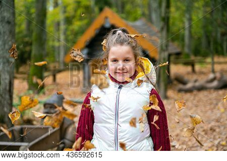 Lovely Girl Has A Fun In Autumn Forest, Kid Enjoy Nature In Autumn Park, Fall Is A Time For Fun