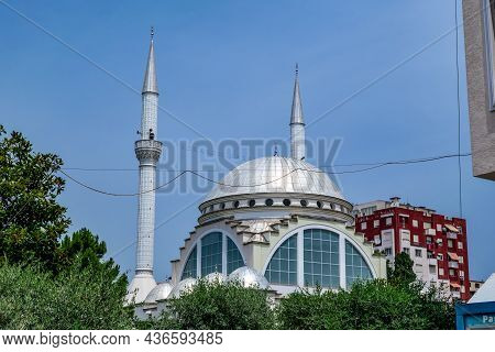 Shkoder, Albania - June 21, 2021: Silver Dome And Two Minarets Of The Ebu Beker Mosque Against The B