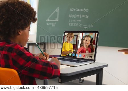 African american boy using laptop for video call, with caucasian elementary school pupils on screen. communication technology and online education, digital composite image.