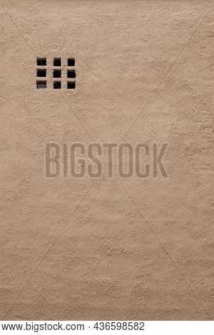 A Vent On The Facade Of A Building Without Windows. Old Brick Plastered Building.