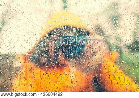 Close Up And Soft Focus Of Raindrops On The Glass With A Blurry Reflection Of A Woman In A Bright Or