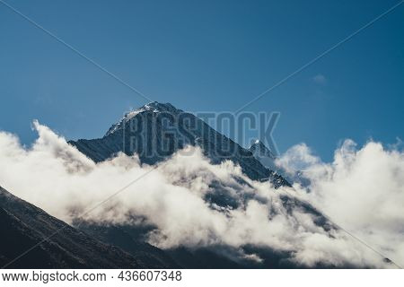 Minimalist View Of Snow-capped Mountain Silhouette Above Thick Clouds. Scenic Mountain Landscape Wit