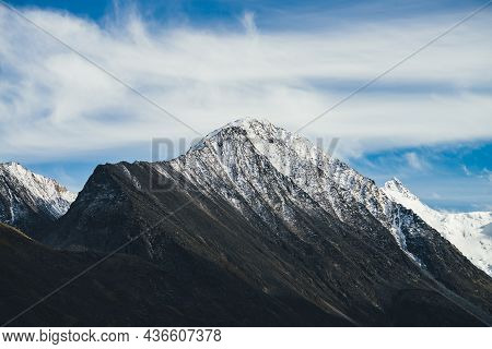 Atmospheric Alpine Landscape With Snow-covered Rocky Mountain Top Under Cirrus Clouds In Blue Sky. A