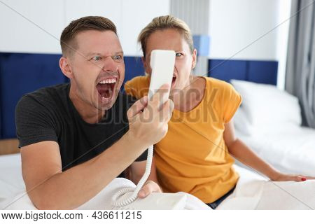 Man And Woman Are Shouting Into Telephone Receiver In Hotel Room