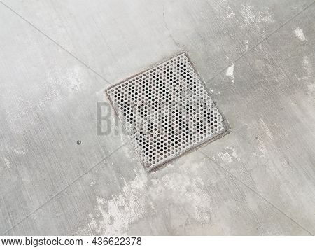 Metal Grate Or Drain With Holes In Cement Floor