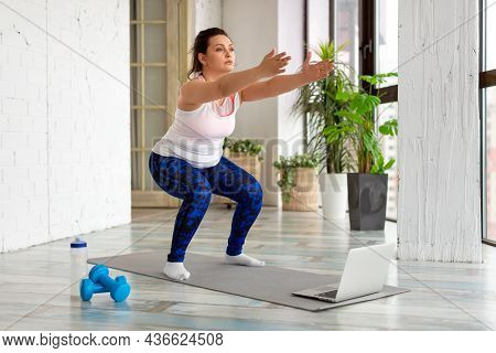 Workout At Home - Middle Aged Woman Performs Squat Exercise While Looking Into A Laptop Monitor. Onl