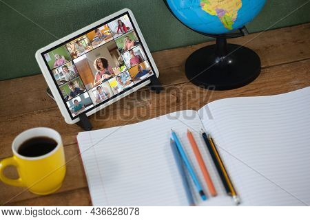 Smiling diverse elementary school pupils during class on tablet screen. communication technology and online education, digital composite image.