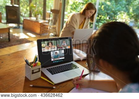 Asian girl using laptop for video call, with smiling diverse elementary school pupils on screen. communication technology and online education, digital composite image.