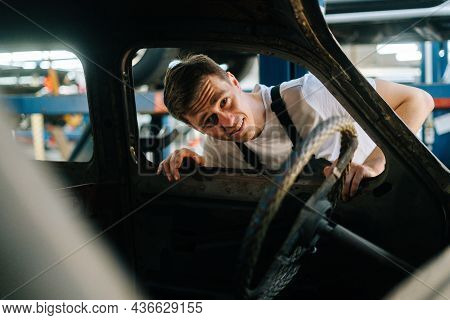 Front View Of Frustrated Young Service Man In Uniform Inspecting Interior Of Old Car In Auto Repair