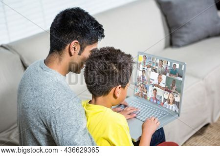 Biracial boy with father using laptop for video call, with elementary school pupils on screen. communication technology and online education, digital composite image.