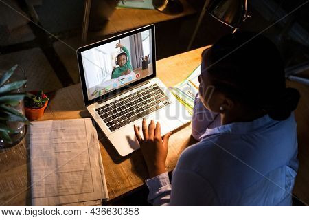 African american woman using laptop for video call, with elementary school pupil on screen. communication technology and online education, digital composite image.