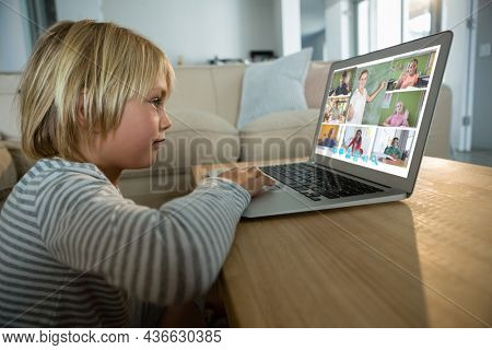 Caucasian boy using laptop for video call, with smiling diverse elementary school pupils on screen. communication technology and online education, digital composite image.