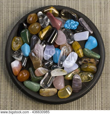 Collection Of Semi-precious Gemstones On Small Black Plate On Grey Textured Background Close Up Top