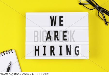 Lightbox With A Words Text We Are Hiring Board On Yellow Background. Surviving Economical And Financ
