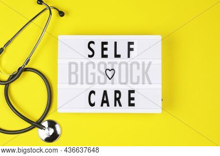 Self-care Word On Lightbox On Yellow Background Flat Lay. Take Care Of Yourself