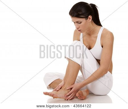 brunette holding her feet on white isolated background poster