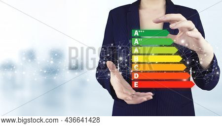 Good Energy Chart Rating. Two Hand Holding Virtual Holographic Energy Efficiency Icon With Light Blu