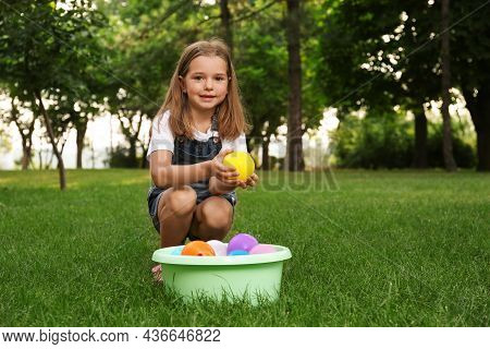Little Girl With Basin Of Water Bombs In Park