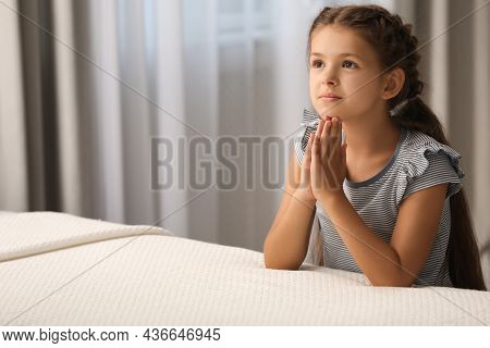 Cute Little Girl With Hands Clasped Together Saying Bedtime Prayer At Home. Space For Text