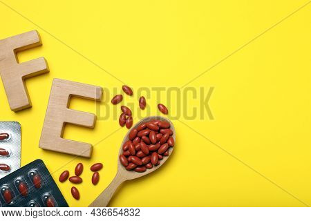 Wooden Letters Fe And Pills On Yellow Background, Flat Lay With Space For Text. Anemia Treatment