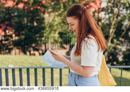 Attractive Young Female Tourist Is Exploring New City. Happy Redhead Woman With Map And Smartphone I