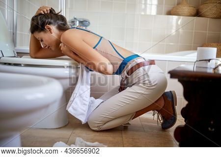 A young girl kneels above the toilet and vomits in the bathroom because of some stomach problem. Toilet, disease, sick