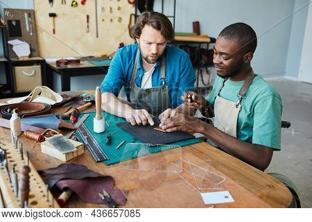 Portrait Of Male Artisan Teaching Young Apprentice Using Wheelchair In Leatherworkers Workshop, Copy