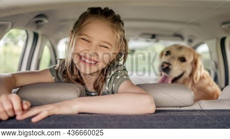 Preteen girl with golden retriever dog sitting in the car, looking at the camera and smiling. Child kid with purebred doggy pet in the vehicle inside