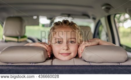 Cute preteen girl with hairstyle sitting in the car, looking at the camera and smiling. Child kid in the vehicle inside during summer trip
