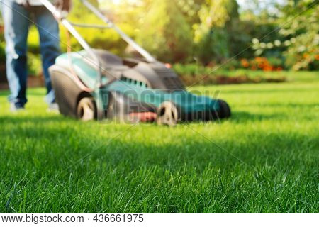 Man Pushing Lawn Mower. Lawn Care Background, Place For Text
