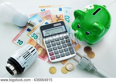 Energy cost, saving energy concept. Piggy bank, calculator and money, plug, bulb and radiator thermostat on white background