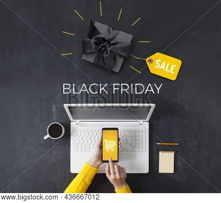Black Friday Advertisement And Black Gift Box On Blackboard. Woman Shopping With Smart Phone App. On