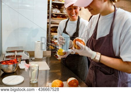 Happy Woman With Grater And Lemon And Colleague Filling Bun With Cream In Bakery