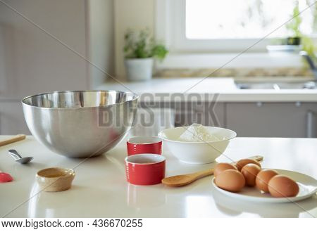 baking ingredients on white kitchen table, baking at home with kids, cake in a mug preparation.
