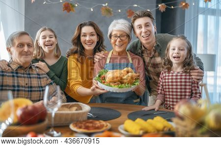 Thanksgiving Day, Autumn feast. Happy family sitting at the table and celebrating holiday. Grandparents, mother, father and children. Traditional dinner.