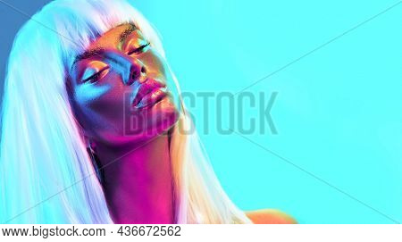 Glowing gold skin. Fashion model woman face in bright neon colourful lights, beautiful sexy woman with white hair and trendy make-up. Art design make up. Glittering, golden, metallic shine makeup