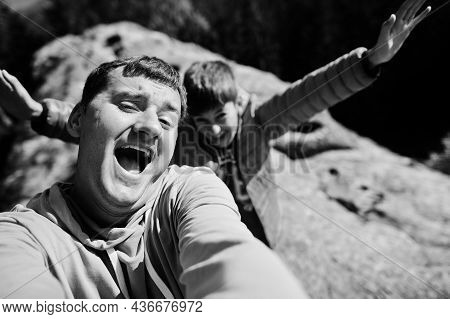 Father With Son. Children Hiking On Beautiful Day In Mountains, Resting On Rock And Admire Amazing V