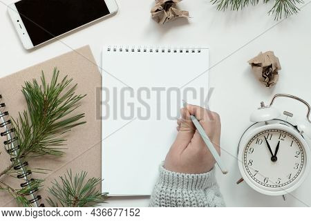 Womans Hand Writing In Empty Notebook. Resolutions, Plan, Goals, Checklist, Idea Concept. Top View,