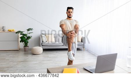 Young Arab Man Stretching His Leg In Front Of Laptop During Domestic Training, Following Online Vide