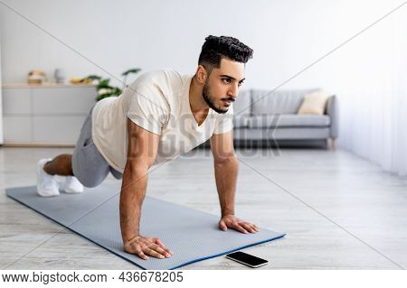 Strength Workout. Fit Young Arab Man Doing Push Ups Or Plank At Home, Following Video Tutorial On Sm