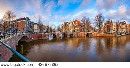 Amsterdam, Netherlands skyline on the bridges and canals at twilight.