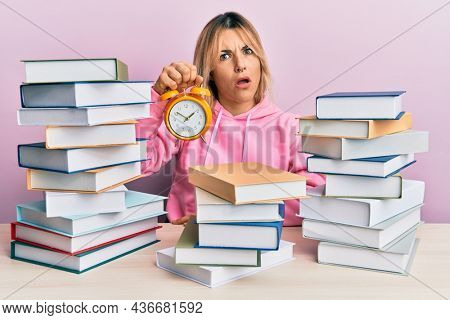 Young caucasian woman holding alarm clock sitting on the table with books in shock face, looking skeptical and sarcastic, surprised with open mouth