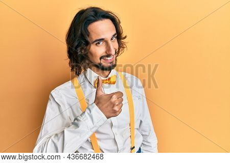 Young hispanic man wearing hipster elegant look doing happy thumbs up gesture with hand. approving expression looking at the camera showing success.