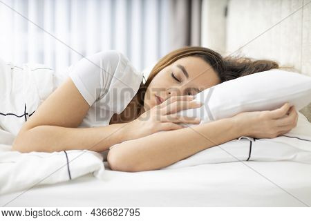 Young Woman Sleeping At Home In Her Bed